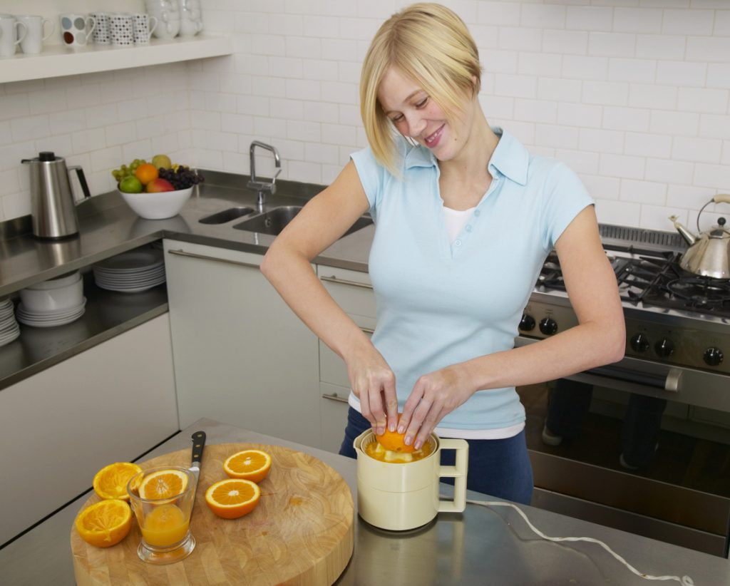 Young woman making orange juice in kitchen, smiling